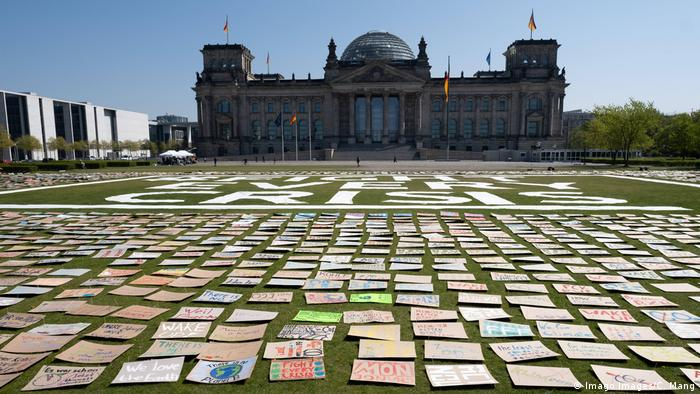 Hundreds of posters calling for climate action laid out in front of the Reichstag building