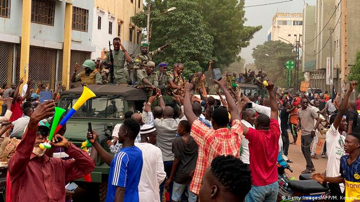 Soldiers are celebrated by a crowd as they arrive in Bamako