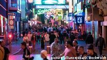01.08.2020, Hamburg: Besucher gehen auf der Reeperbahn durch die Straße Große Freiheit. An Wochenenden gilt derzeit jeweils zwischen 20.00 und 6.00 Uhr ein Alkoholverkaufsverbot. Foto: Daniel Bockwoldt/dpa | Verwendung weltweit