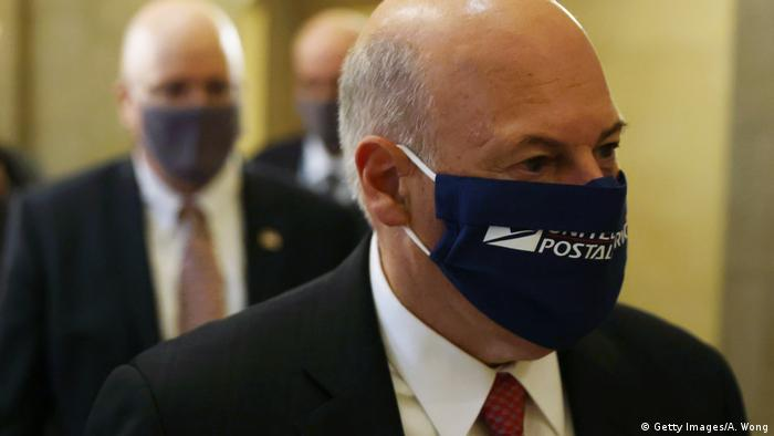 Louis DeJoy wears a face mask with the logo of the USPS on it