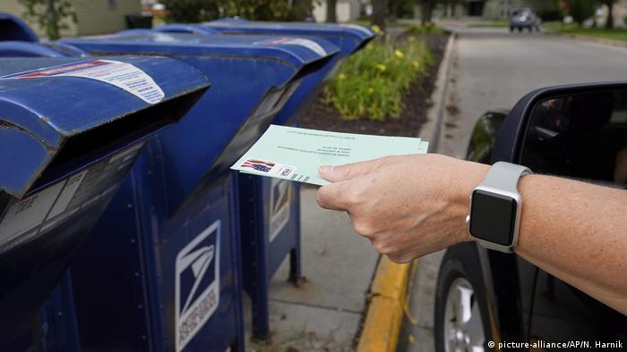 Mão coloca carta numa caixa de correio