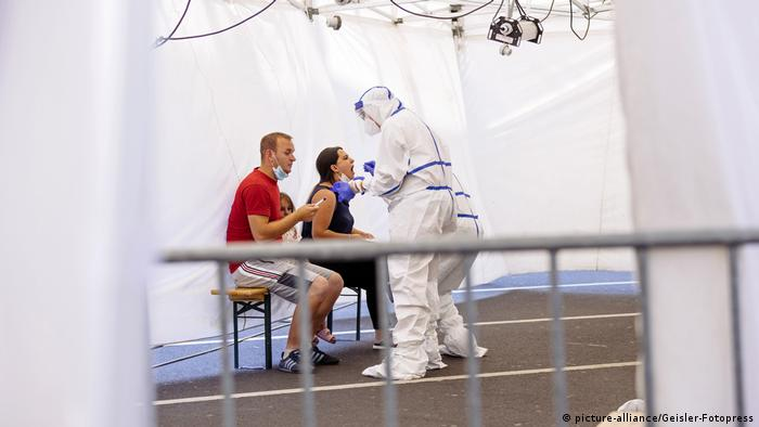 A health worker administers COVID-19 tests to two travelers inside a tent at Cologne-Bonn Airport (picture-alliance/Geisler-Fotopress)