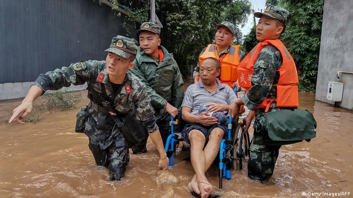Police officers evacuating a resident on a flooded street in China's Sichuan province