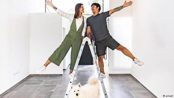 Casal sobre escada sob a qual cachorro olha para a câmera