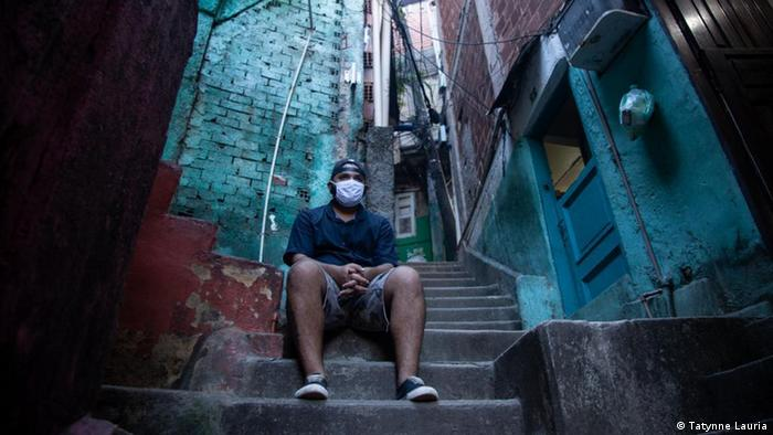 Homem de máscara sentado em escada de favela no Rio de Janeiro