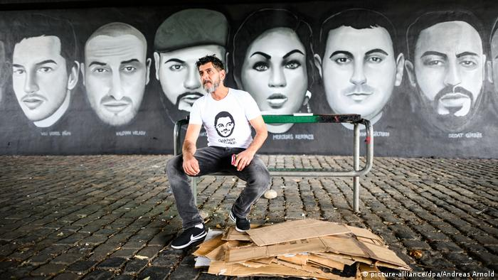 Cetin Gültekin in front of a mural of the victims of Hanau (picture-alliance/dpa/Andreas Arnold)