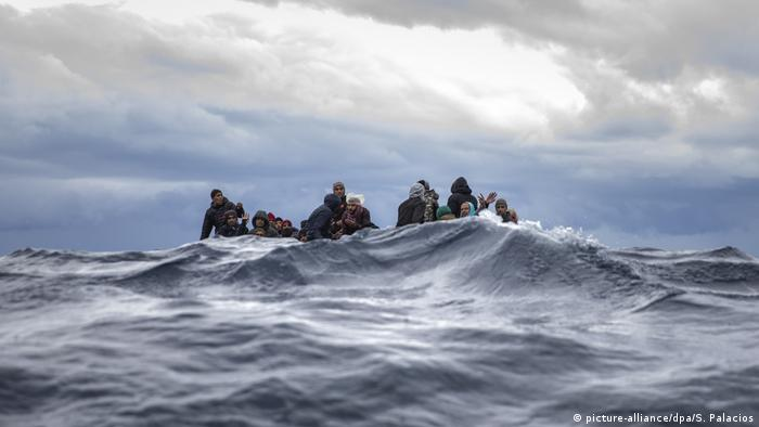 Men sitting in overcrowded wooden boat off Libya
