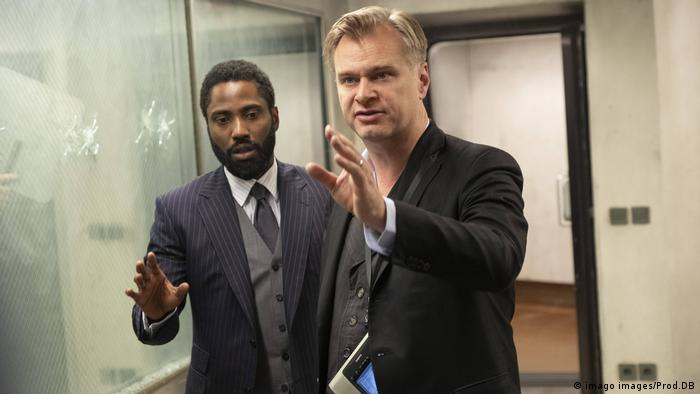 Christopher Nolan gives instructions on set during the filming of his film, 'Tenet.' Actor John David Washington stands next to Noland