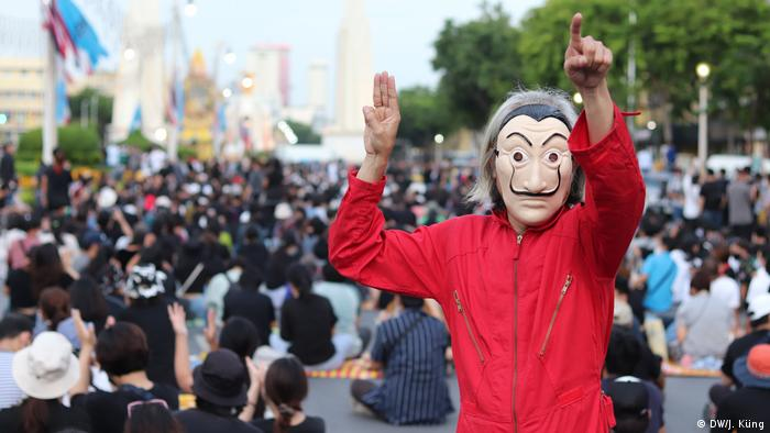 A protester in Thailand wearing a face mask and a red jacket