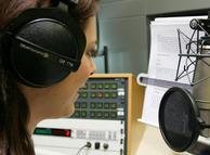 Ведущая на радио читает в миркофон
