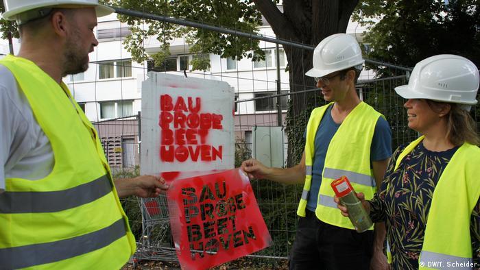 Daniel Wetzel, Stefan Kaegi und Helgard Haug vom Rimini Protokoll stehen mit Bauarbeiterhelmen und Schutzwesten vor der Beethovenhalle in Bonn