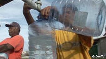 Mann füllt Wasser in Kanister (Quelle: DW)