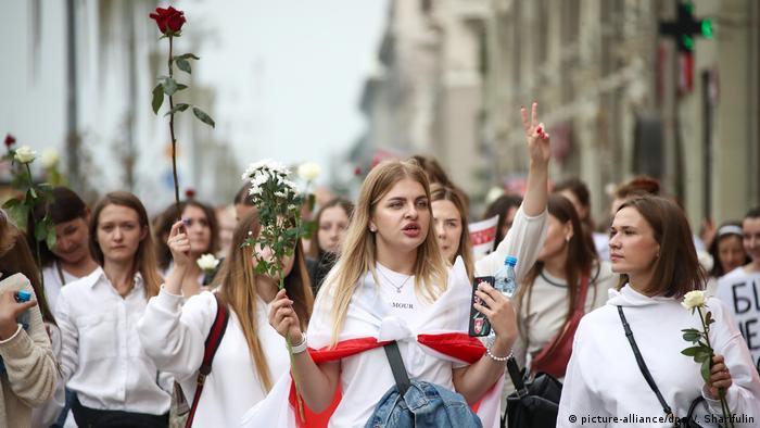 Junge Frauen demonstrieren weiß gekleidet und mit Blumen in den Straßen von Minsk (picture-alliance/dpa/V. Sharifulin)