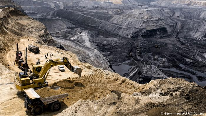 An excavator loads soil onto a truck at a open coal mine near Mahagama in the Indian state of Jharkhand