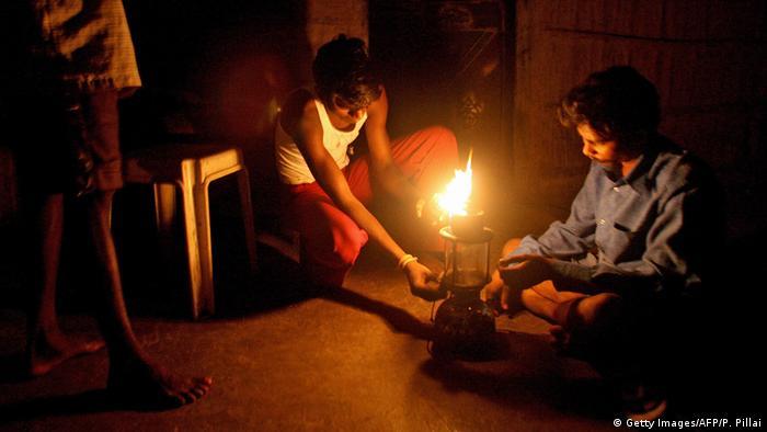 Men with kerosene lamp on the outskirts of Mumbai