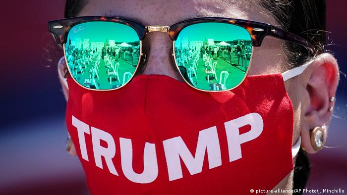 A person wearing sunglasses and a red mask that says Trump on it