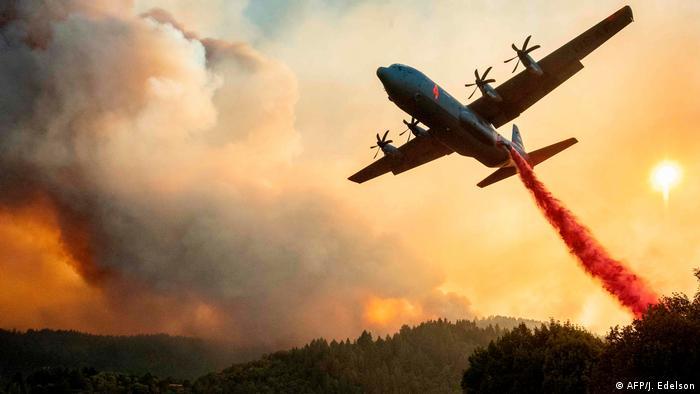 As tthe forest burns, an aircraft drops fire retardant on a wooded ridge