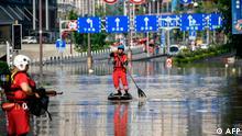 TOPSHOT - This photo taken on August 19, 2020 shows a rescuer paddling across a flooded street in China's southwestern Chongqing. - Floods in mountainous southwest China have washed away roads and forced tens of thousands from their homes, with authorities warning on August 19 the giant Three Gorges Dam was facing the largest flood peak in its history. (Photo by STR / AFP) / China OUT