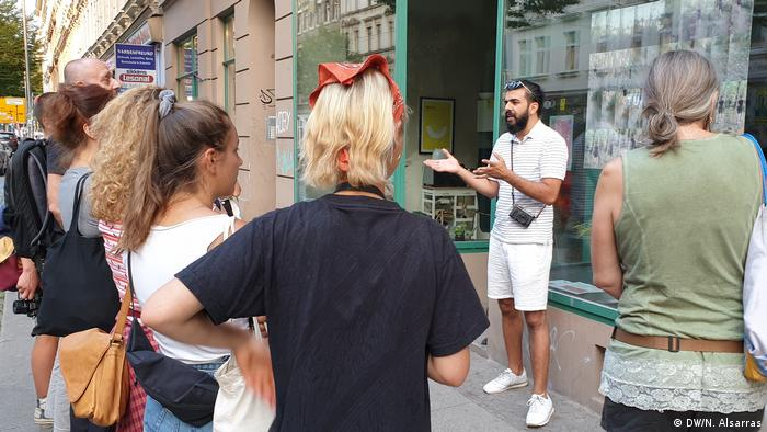 ریسان حمید از آثار هنری خود برای رهگذران سخن میگوید، لایپزیگ، خیابان آیزنباناشتراسه