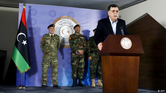 Libyens Ministerpräsident Fayiz as-Sarradsch steht an einem Rednerpult, hinter ihm stehen Offiziere in Tarnanzügen (AFP)