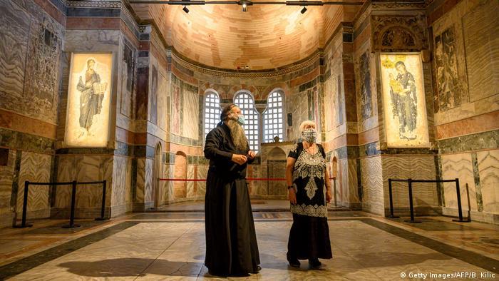 Geistlicher und Besucherin mit Mund-Nase-Masken stehen im Kariye Museum, der ehemaligen Chora-Kirche in Istanbul/Türkei (Getty Images/AFP/B. Kilic)