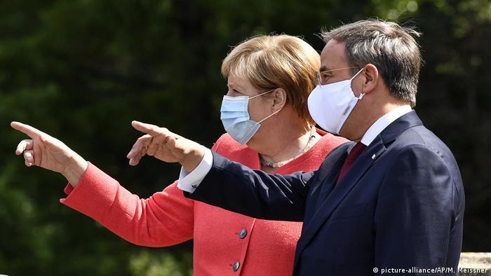 Армин Лашет и Ангела Меркель показывают пальцами в одну сторону