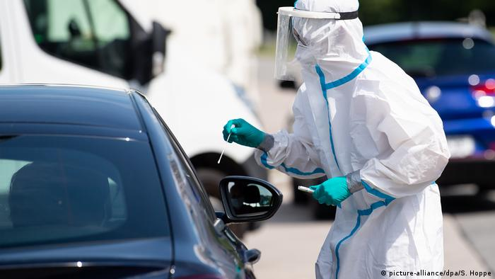 Man in protective gear and swab at motorway testing station