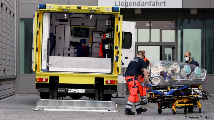 German paramedics push a stretcher at the entrance of the Charite hospital in Berlin