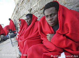 african refugees wrapped in blankets in spain