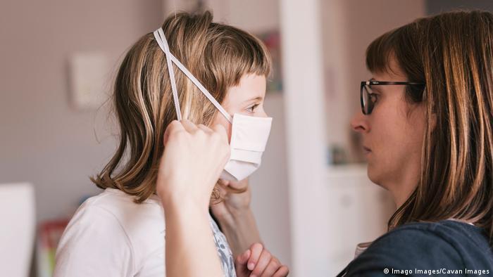 Mutter zieht ihrer Tochter Zuhause eine Schutzmaske über