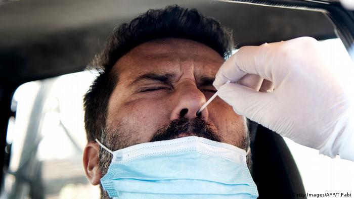 Einem Man wird ein Wattestäbchen in die Nase gesteckt, er verzieht das Gesicht vor Schmerzen