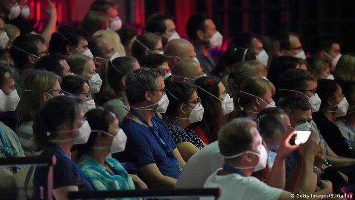 Participants wearing FFP2 protective face masks watch watching a concert, one of them taking a photo with their smartphone