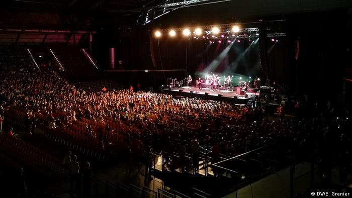 In einer großen Halle sitzen in einem halb besetzten Saal Zuschauer, auf der beleuchteten Bühne stehen Rockmusiker (Foto: DW/E. Grenier).