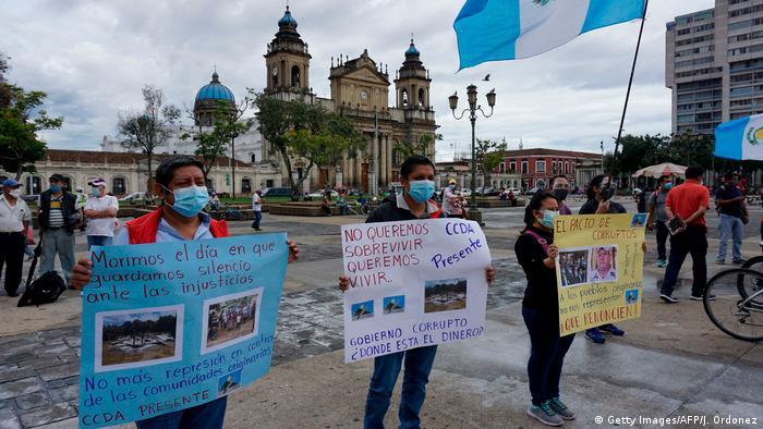 People hold signs demanding he resignation of Guatemalan President Alejandro Giammattei amid the coronavirus pandemic