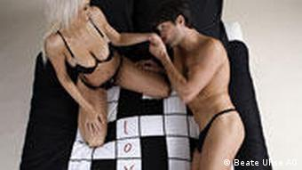 A man and a woman on bed covers with love and sex written on them