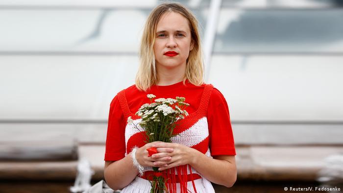 Eine Frau in rot-weiß-roter Kleidung hält weiße Blumen (Reuters/V. Fedosenko)