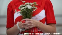23.08.2020, Belarus, Minsk: MINSK, BELARUS - AUGUST 23, 2020: A woman holds flowers as she takes part in a 'chain of solidarity' formed by Belarusian women in Independence Square. Since the announcement of the 2020 Belarusian presidential election results on August 9, mass protests against the election results have been hitting major cities across Belarus. Natalia Fedosenko/TASS Foto: Natalia Fedosenko/TASS/dpa  