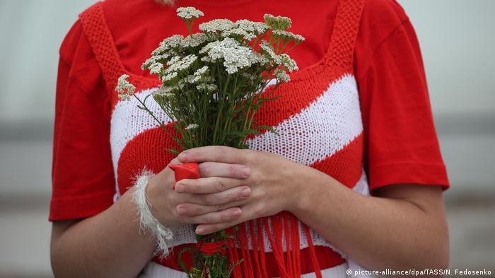 На Площади независимости выстроились в цепь женщины, держа в руках цветы, бело-красно-белые флаги и плакаты.