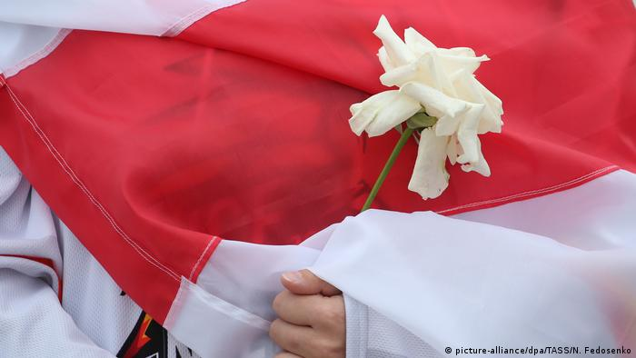 Девушка, закутанная в бело-красно-белый флаг, держит в руках гвоздику