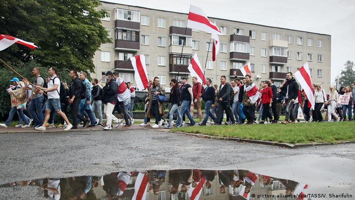 A picture of striking factory workers at a tractor plant in Minsk, who are waving Belarusian flags and holding up protest placards during their walkout