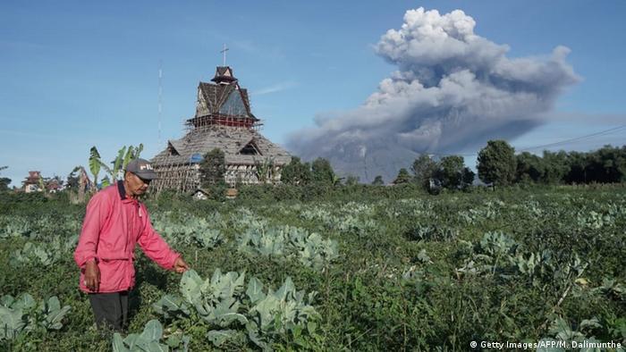 Seorang petani bekerja di sebuah pertanian saat Gunung Sinabung mengeluarkan asap tebal ke udara di Karoo