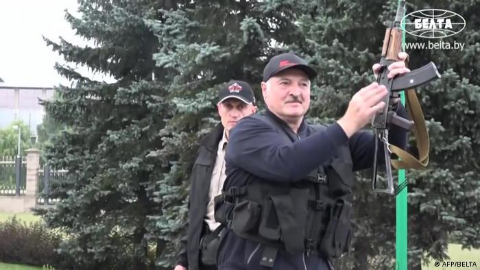 Александр Лукашенко прилетел на вертолете к президентской резиденции, Дворцу независимости. На нем бронежилет, в руках - автомат.
