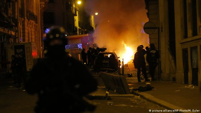 French police officers watch a car burning near the Champs-Elysee avenue (picture-alliance/AP Photo/M. Euler)