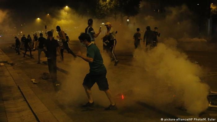 PSG supporters run through tear gas sent by police forces the Champs-Elysee avenue (picture-alliance/AP Photo/M. Euler)