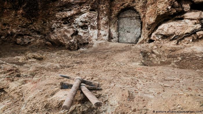Zwei Spitzhacken liegen vor einer Höhle, die mit eienr Tür verschlossen ist (picture-alliance/zumapress.com)