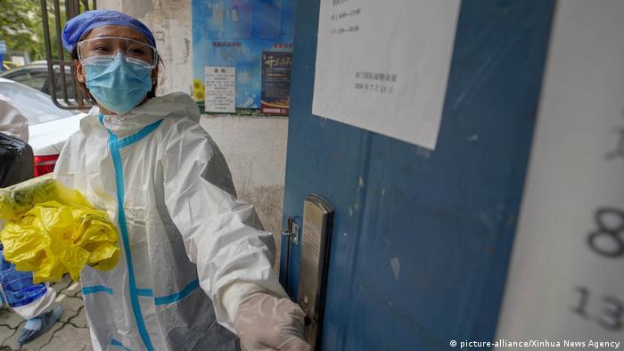 China Helfer Qiu Tingting sammelt den Müll von Bewohnern in Quarantäne ein