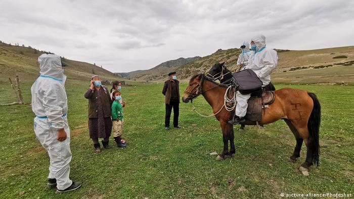 China, Polizisten helfen Menschen im Kampf gegen den COVID-19 in Altay