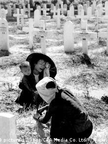 Duas mulheres e uma criança choram em um cemitério com cruzes ao fundo no final da Primeira Guerra da Indochina (contra os franceses), em 1954