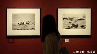 Visitante vê fotos de Robert Capa em uma exposição em homenagem ao centenário do fotógrafo em Seul, capital da Coreia do Sul, em agosto de 2013.