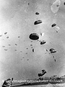 Em fotografia de Robert Capa, paraquedistas americanos pousam na Alemanha nazista em março de 1945